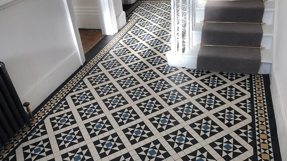 Victorian mosaic hall floor ceramic tiles in a palette of black, white, blue and yellow. Stair runner and brass rods.