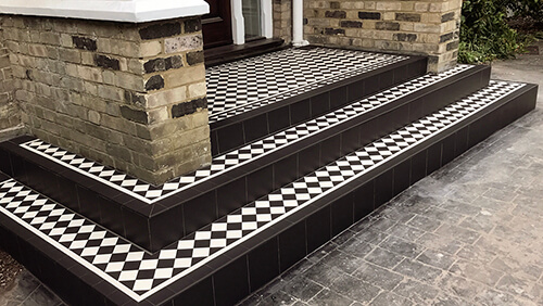 Classic chequerboard design on a set of wide entrance steps with brick piers.