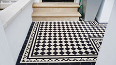 Black and White Victorian Garden Tiles - Traditional Yorkstone steps and a daisy grate for cellar ventilation.