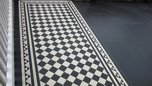 Black and white path tiles installed alongside slate slabs - a popular combination and easy to maintain front garden design.