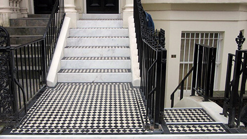 Traditional black and white tiles supplied along with carrara marble risers for a classic finish.