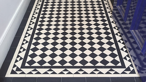 A traditional black and white chequerboard with decorative pyramid border alongside a navy blue gloss painted door.