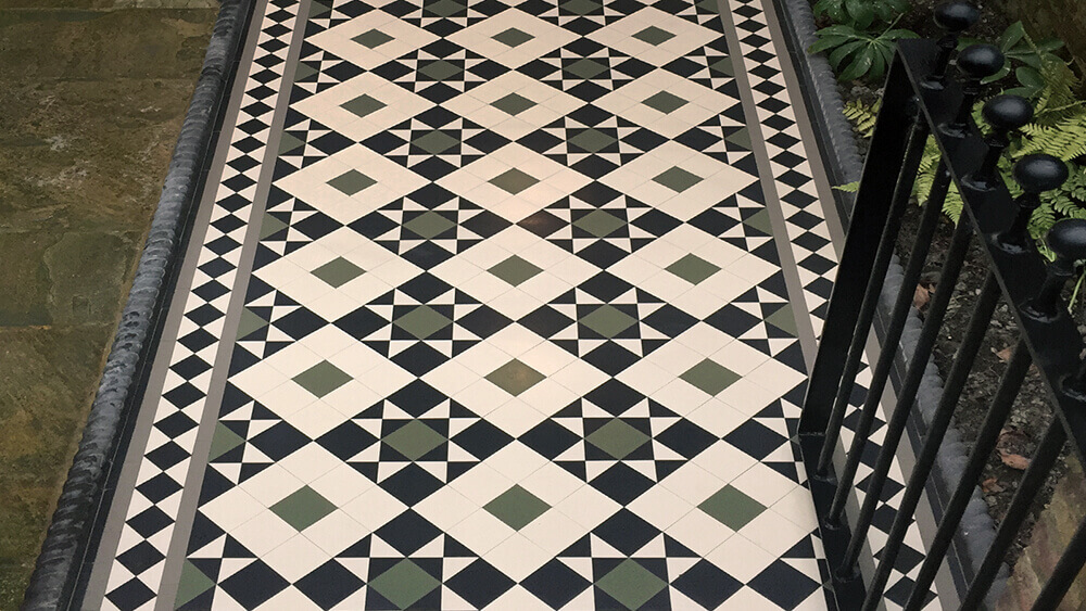 Victorian black, white and grey path tiles with rope top edging and iron gate. Stone slabs complete the garden.