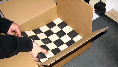 Sheets of Victorian black and white chequered tiles being put into box