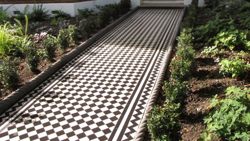 New installation of traditional Victorian black and white mosaic path tiles