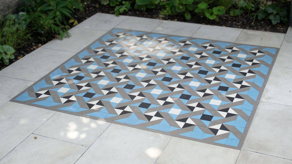 Modern geometric ceramic tile garden feature - Berkeley 70 pattern: Black, White, Grey and Pale Blue, a modern optical design. Here we see a perfect example of how our geometric floor tile range can be used in a more contemporary setting, framed by sand stone slabs.